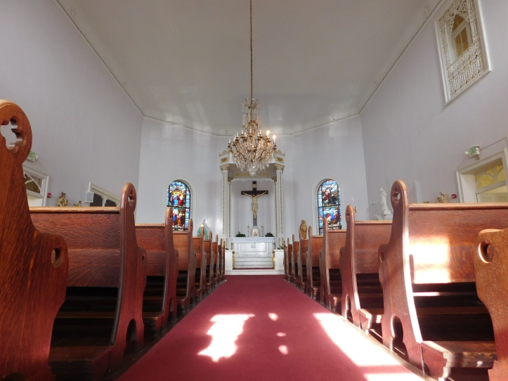 The pews and the beautiful cross and stained glass windows in the main chapel.